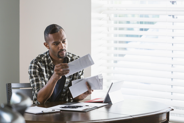 Young man reviewing bills at laptop